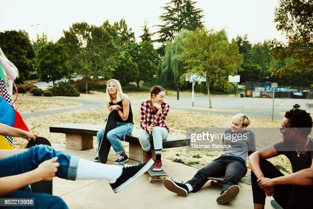 Group of female skateboarders in discussion while hanging out at skate park