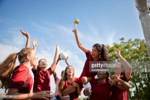 grupo de jugadoras de fútbol que celebran la victoria con trofeo - the championship competición de fútbol fotografías e imágenes de stock