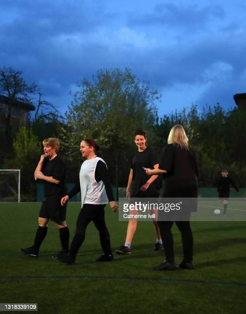 group of female soccer players leaving pitch after finishing a match at night - menopossibilities stock pictures, royalty-free photos & images