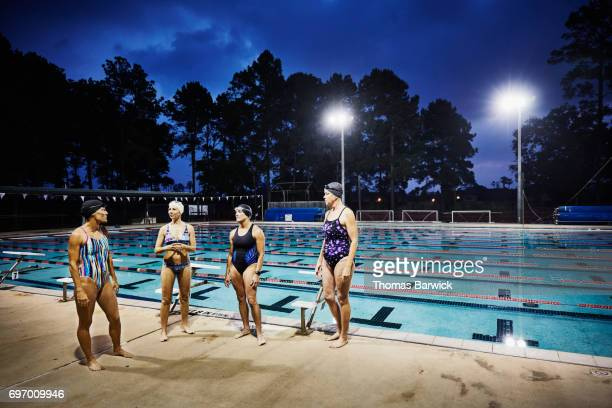 Group of female swimmers in discussion on outdoor pool deck before early morning workout