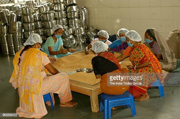Group of female workers cleans the food grains / Pulses at the Kitchen of Isckon Food Relief Foundation in Delhi India
