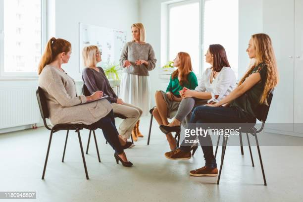 group of females discussing during therapy session - izusek stock pictures, royalty-free photos & images
