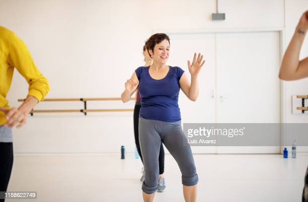 group of females practicing zumba - fat lady in leggings stock photos and pictures