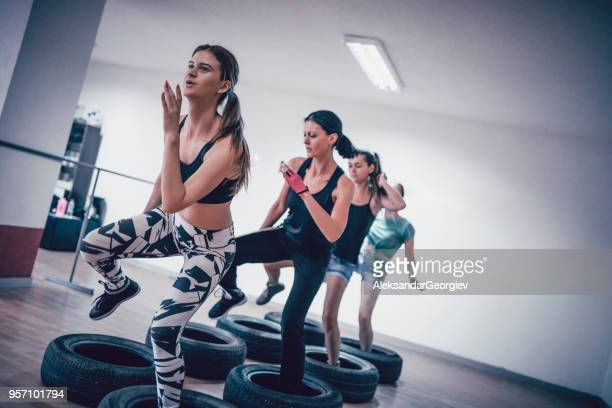 group of females receiving tire obstacle course training in gym - military style stock pictures, royalty-free photos & images