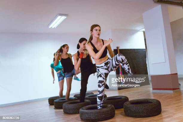Group Of Females Receiving Tire Opstacle Cours Training in Gym