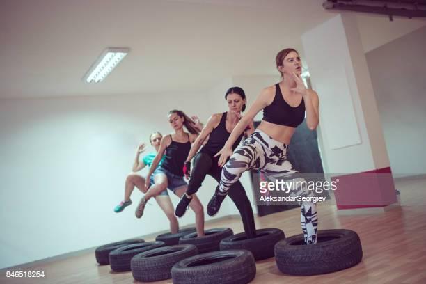 Gruppe von Frauen empfangen Reifen Opstacle Cours Training im Fitness-Studio
