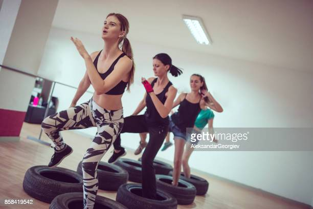 group of females receiving tire opstacle cours training in gym - military training stock pictures, royalty-free photos & images