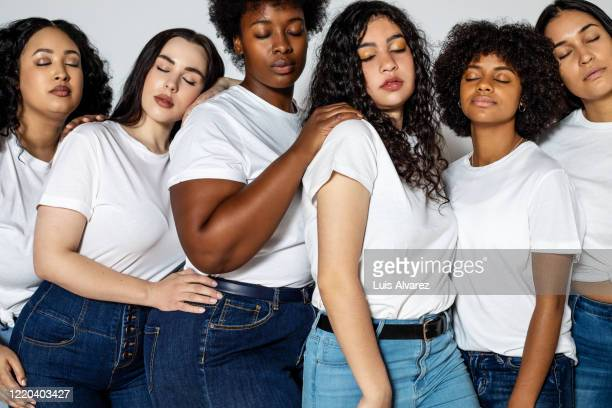 group of females standing together with their eyes closed - jeans stock pictures, royalty-free photos & images
