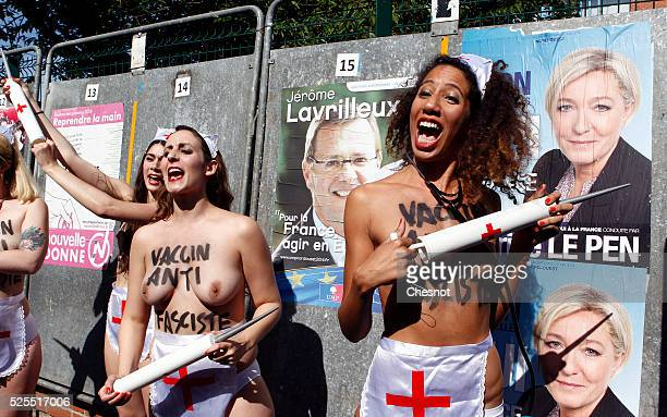 A group of Femen activists stand in front of an electoral banner of French farright Front National party president Marine Le Pen near a polling...