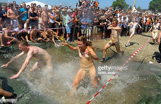 A group of festivalgoers run in the annual Naked Run at the camp site on day 3 of the Roskilde Festival on July 3 2010 in Roskilde Denmark
