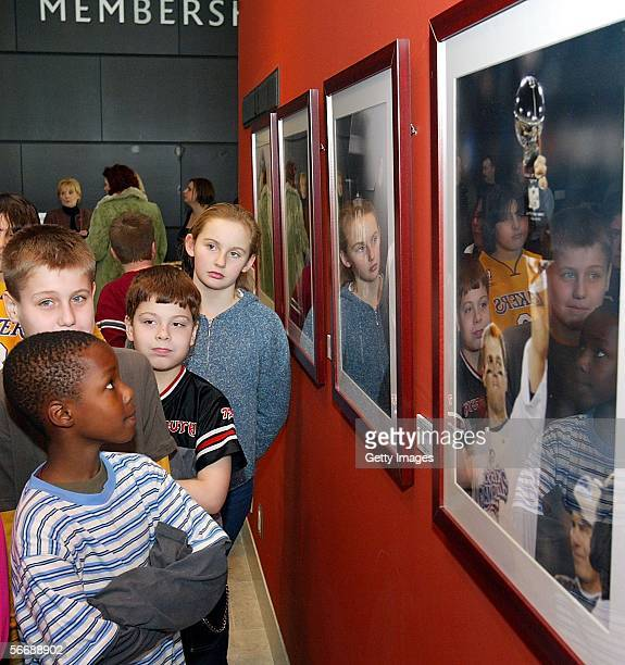 A group of fifth grade students take time to look at photographs during the Getty Images '40 Years of Football' photo display unveiled at the Art...