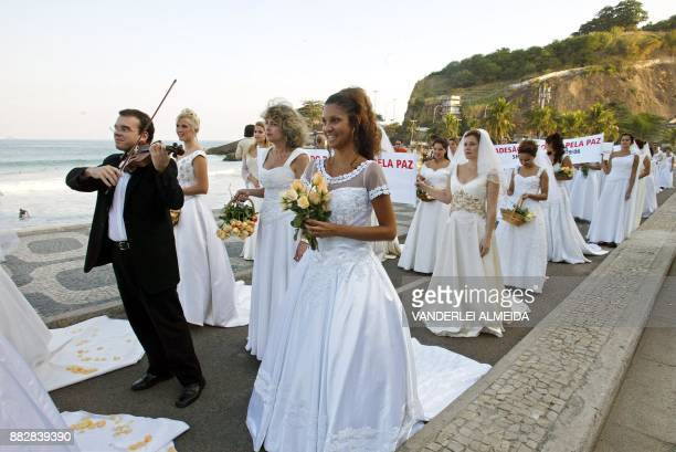 A group of fifty brides carrying banners march along Leblon beach in the southern part of Rio de Janeiro 26 June 2003 The brides were protesting...