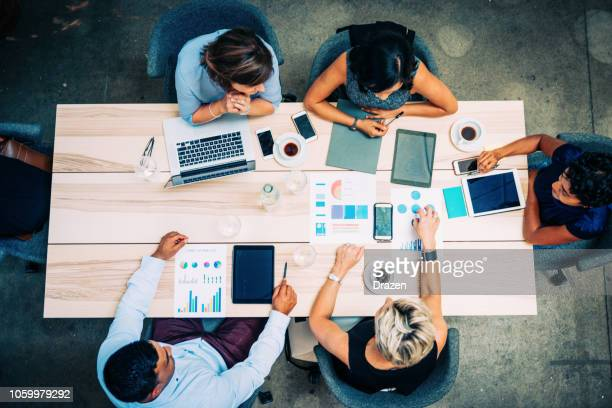 group of financial professionals analyzing markets - società foto e immagini stock