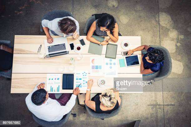 group of financial professionals analyzing markets - directly above stock pictures, royalty-free photos & images