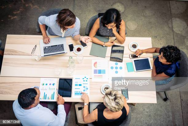 group of financial professionals preparing tax paperwork - minority groups stock pictures, royalty-free photos & images