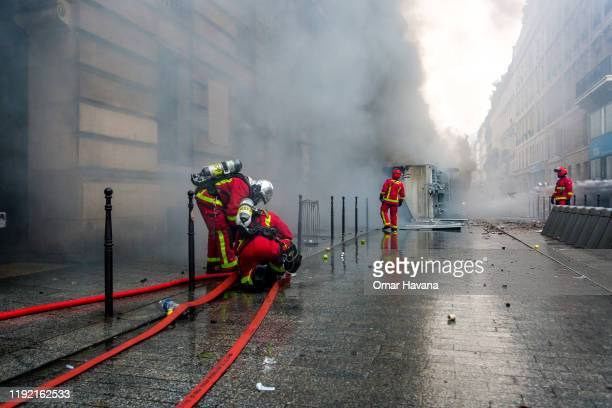 A group of firefighters extinguish a truck set on fire by radical groups during the first day of an indefinite general strike on December 05 2019 in...