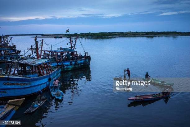 A group of fisherman gather to catch fish next to fishing boats docked in the harbor in Puducherry India on Saturday July 19 2014 Indias gross...