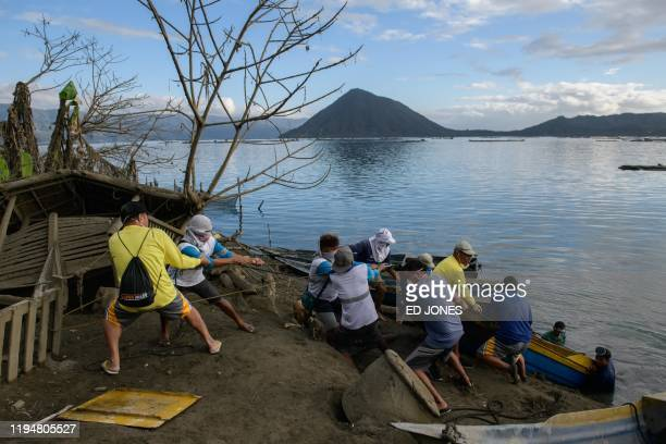 A group of fishermen haul a boat from the water as they make repairs to their operations affected by the eruption of the Taal volcano in Buso Buso on...