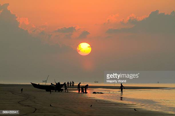 A group of fishermen haul their boat ashore at Kuakata beach This is one of the rare natural spots that offers a full view of the rising and setting...