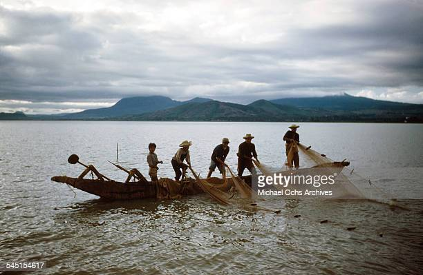 A group of fishermen in a boat pull up a fishing net on the lake in Patzcuaro Michoacan Mexico