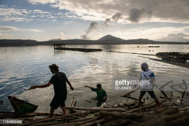 A group of fishermen make repairs to their operations affected by the ashfall from the eruption of the Taal volcano in Buso Buso on January 20 2020...