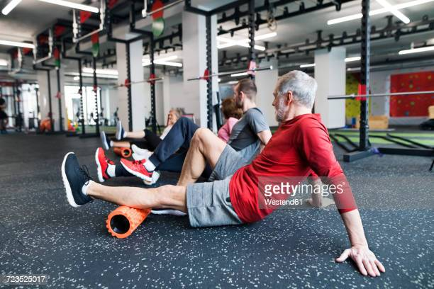 Group of fit seniors in gym using foam rollers