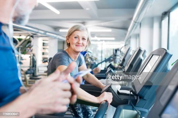 Group of fit seniors on treadmills working out in gym, woman smiling