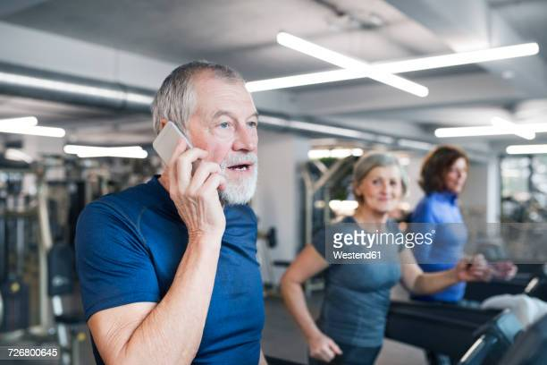 Group of fit seniors working out on treadmills in gym, man with smart phone
