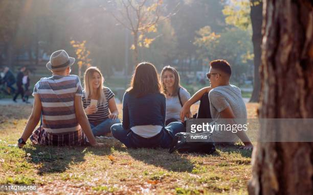 group of five friends laughing out loud outdoor, sharing good and positive mood - leisure activity stock pictures, royalty-free photos & images