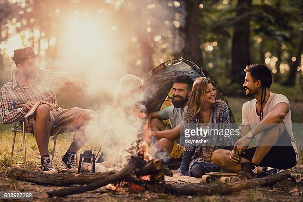 group of five happy friends enjoying around campfire. - lagerfeuer stock-fotos und bilder