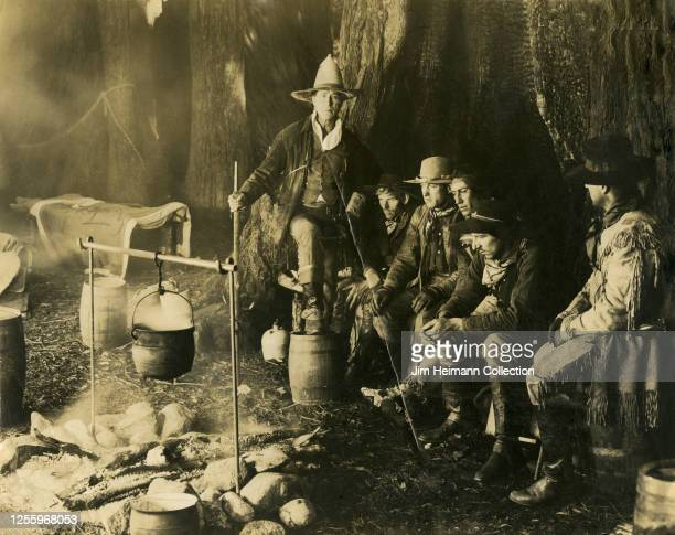 Group of five men in Western cowboy attire are gathered around a campfire with a Native American scout, circa 1918.