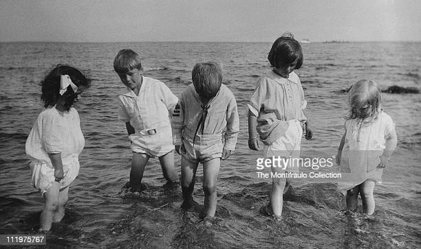 Group of five young children in summer clothes paddling in the sea off the coast of America circa 1924 some ships can be seen in the far distance