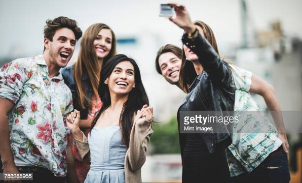 A group of five young people standing on a rooftop posing for a selfie.