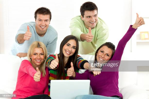 Group of five young people working on laptop computer indoors