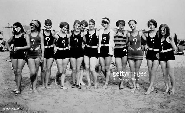A group of flappers with question marks on their swim suits pose together on the beach