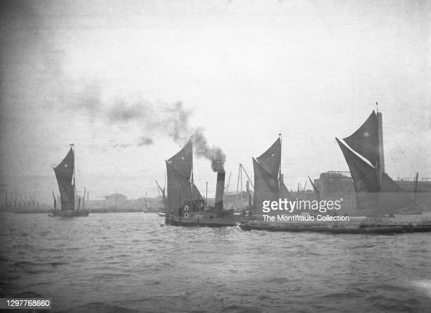 Group of flat bottomed Thames barges with a tug boat passing between them sailing in convoy on River Thames with industrial buildings and cranes in...