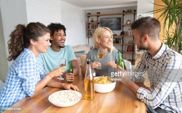 Group of flat mates having drinks at home