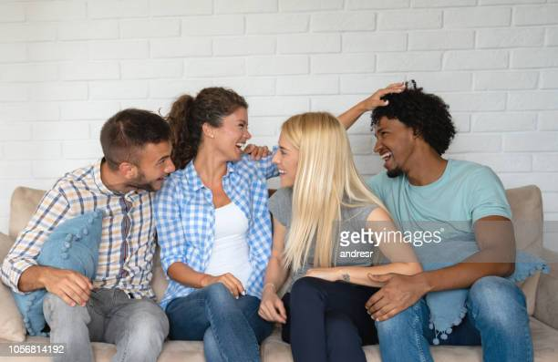 Group of flat mates having fun sitting on the sofa and smiling