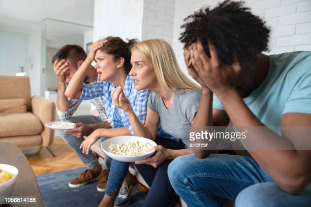 Group of flat mates watching sports at home