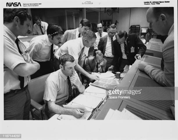 A group of flight controllers gather round the console of Shift 4 flight director Glynn Lunney in the Missions Operations Control Room of the Mission...