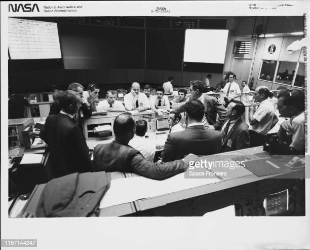 A group of flight controllers in the Missions Operations Control Room of the Mission Control Center at the Manned Spacecraft Center in Houston Texas...