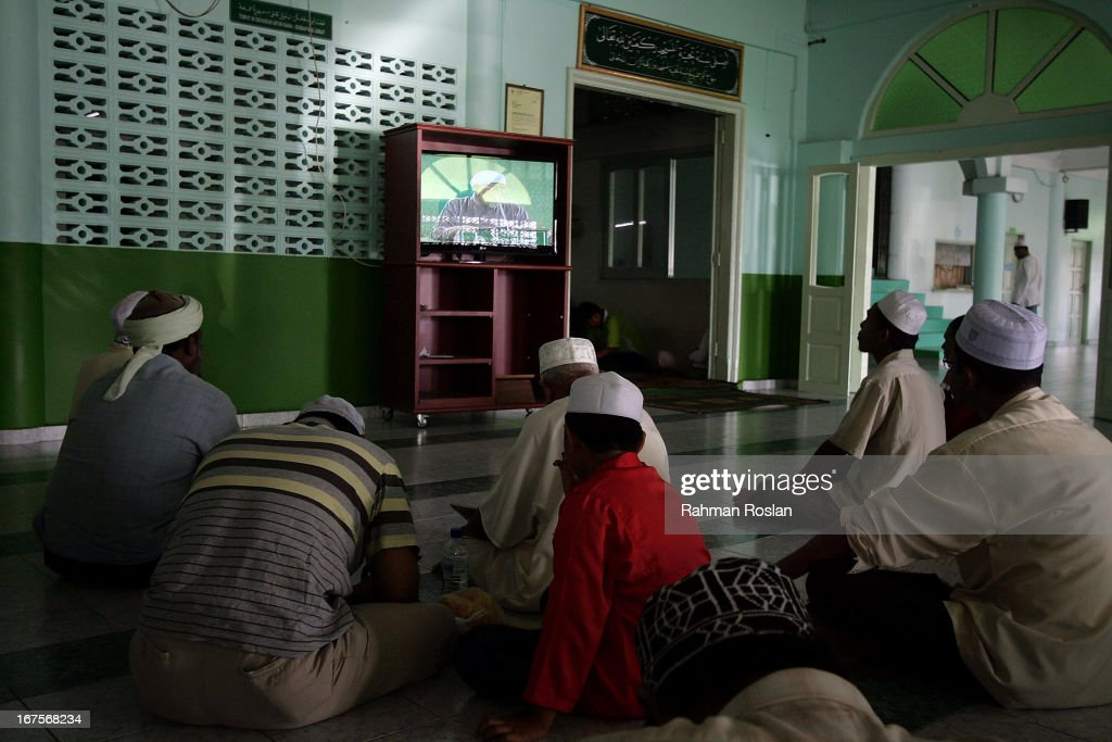 A group of followers and Koran students listen to Hadi Awang's weekly friday sermon through a live telecast on April 26, 2013 in Rusila, Malaysia. Malaysia's 13th general election will be held on May 5.