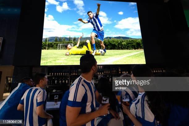 grupp av fotbollsfans som tittar på spelet på en bar - tävlingsomgång bildbanksfoton och bilder