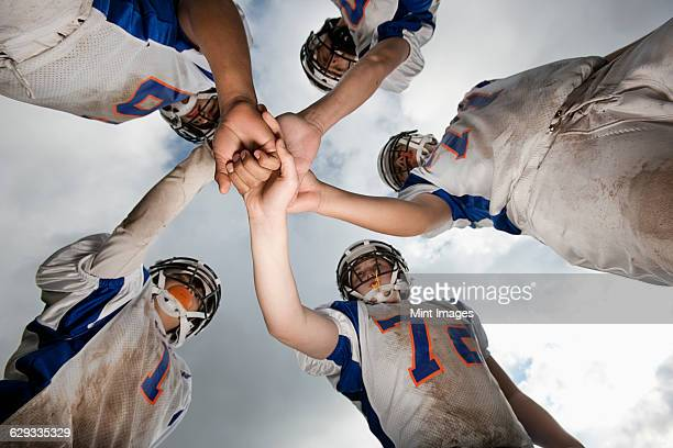 a group of football players, young people in sports uniform and protective helmets, in a team huddle viewed from below.  - huddling stock pictures, royalty-free photos & images