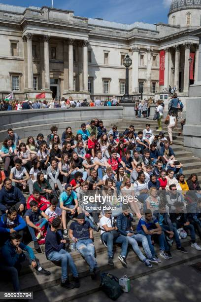 A group of foreign students sit on the steps in Trafalgar Square on 9th May 2018 in London England