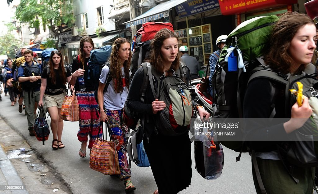 A group of foreign tourists walk in line in the ancient quarters of Hanoi on December 21, 2012. More than six million international visitors arrived in Vietnam during the first 11 months of 2012, representing a 11.4 percent growth over the same period last year, according to official statistics. AFP PHOTO/HOANG DINH Nam