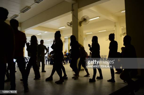 A group of foreign women rounded up by police from karaoke bars in Thailand's southern province of Narathiwat are taken to city hall during a...