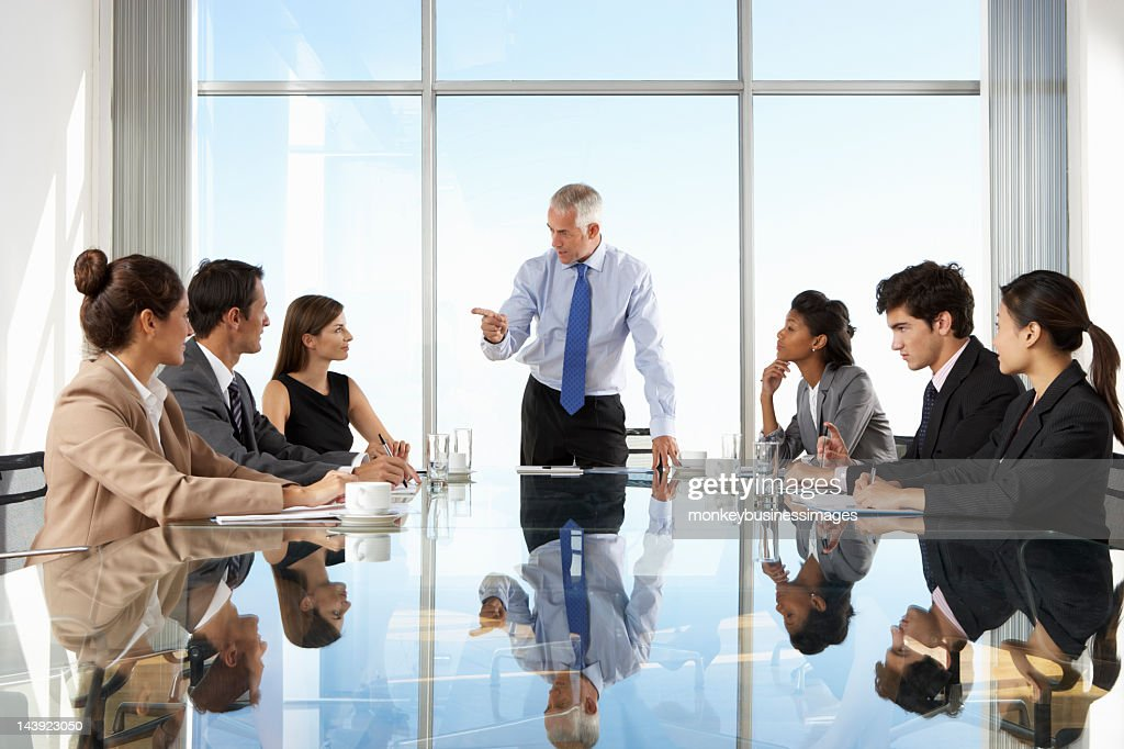 Group of formal business people having a board meeting : Stock Photo