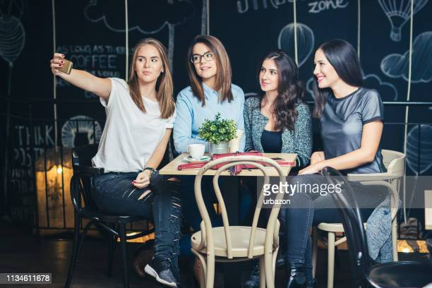 group of four best girlfriends in a cafe relaxing and make selfi - four people stock pictures, royalty-free photos & images