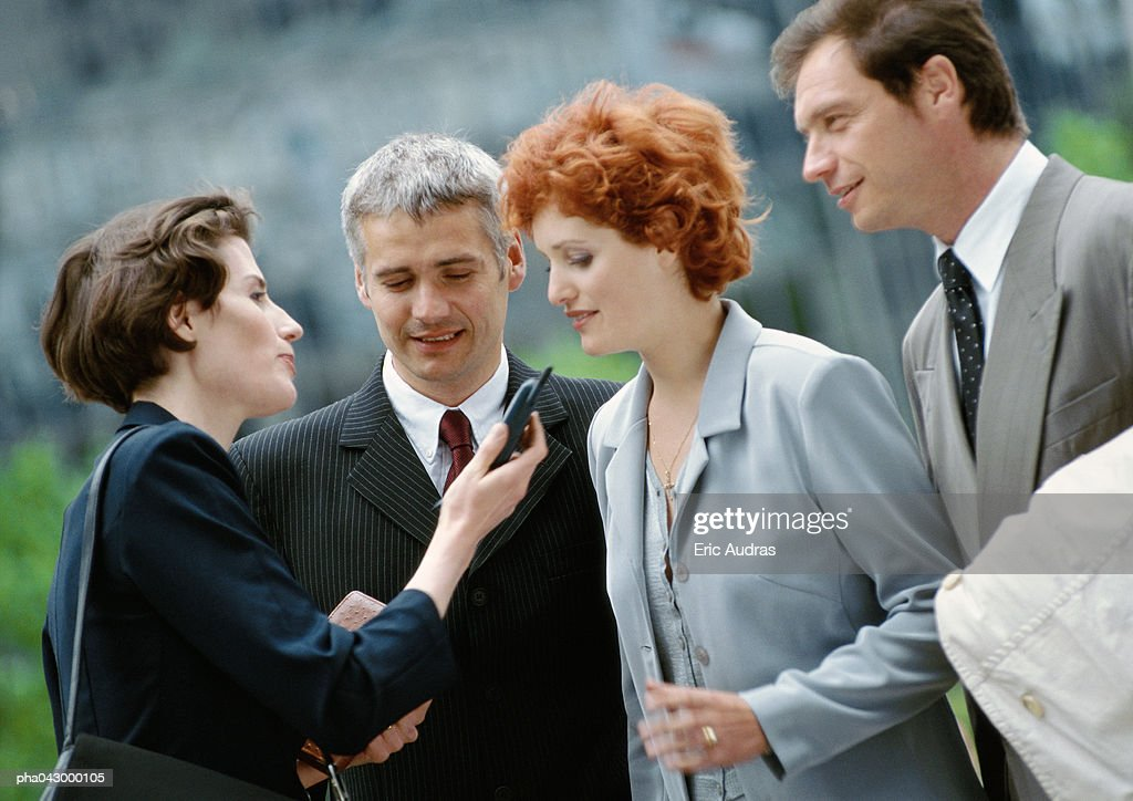 Group of four business people outside, one holding cell phone : Stockfoto